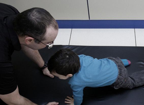 A través de juegos, los fisioterapeutas ayudarán al niño con daño cerebral a realizar ejercicios de movilidad.
